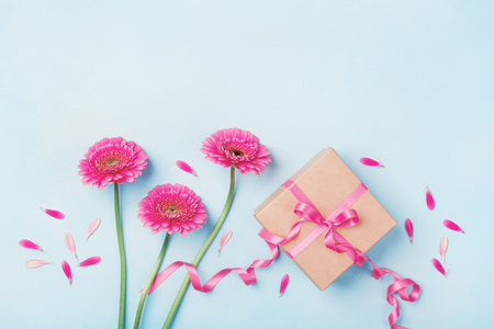 Frühlingszusammensetzung mit rosa Blumen und Geschenkbox auf blauer Tischplatteansicht. Grußkarte für Geburtstag, Frau oder Muttertag. Flach liegen. Standard-Bild