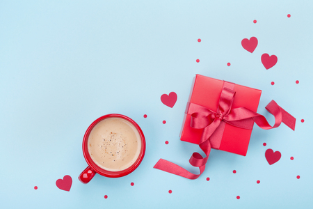 Breakfast for Valentines day. Coffee, gift box, paper heart and confetti on blue background top view. Empty space for text. Flat lay.