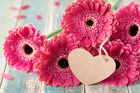 Beautiful bouquet from gerbera daisy flowers with greeting note in shape of heart for valentines, womans or mother day on wooden vintage background.