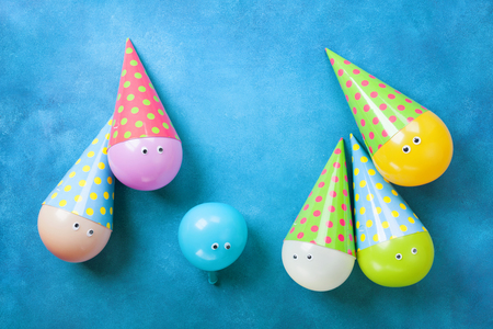 Colorful funny balloons in caps on blue table top view. Creative concept for birthday party background. Flat lay.