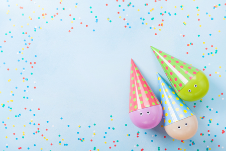 Funny birthday or party background. Colorful balloons and confetti on blue table top view. Flat lay. Greeting card.