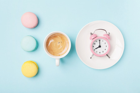Morning cup of coffee, cake macaron and alarm clock on light turquoise table top view. Flat lay style. Beautiful breakfast. Sweet macaroons. Stock Photo