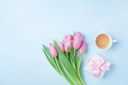 Spring card for Womans or Mothers Day. Gift box, tulip flowers and cup of coffee on blue pastel table top view. Flat lay.