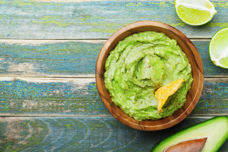Green guacamole with  ingredients avocado, lime and nachos on wooden vintage table top view. Traditional mexican food.