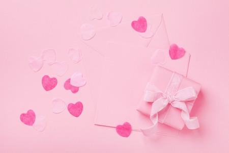 ファッションパステルモックアップ。ピンクのテーブルトップビューにギフトまたはプレゼントボックスと封筒。バレンタイン、女性や母の日のた 写真素材