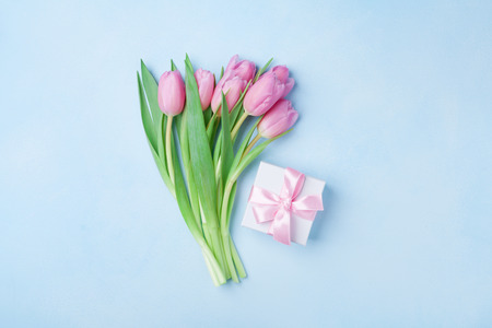 Spring tulip flowers and gift box on blue pastel table top view. Greeting card for Birthday, Womans or Mothers Day. Flat lay.