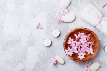 Aromatherapy, spa, beauty background with massage pebble, perfumed flowers water and candles on stone table top view. Relaxation and zen like concept. Flat lay style.