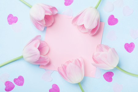 Birthday or wedding mockup with pink paper list, hearts and tulip flowers on blue background top view. Beautiful woman day card. Flat lay.
