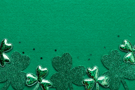 Saint Patricks Day border with shamrock on green background from above.