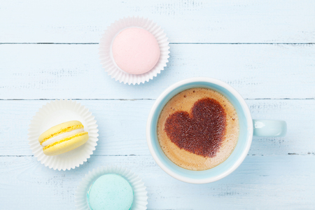 Cake macaron or macaroon and cup of coffee with heart on foam top view. Flat lay style.
