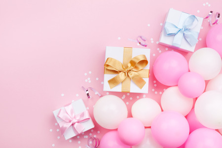Birthday background with gift or present box, balloons and confetti on pink pastel table top view. Flat lay style.
