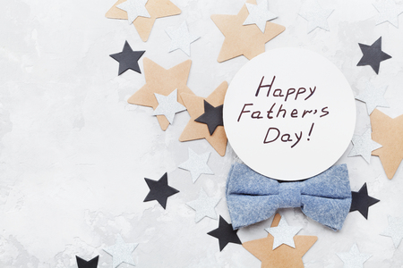 Happy Fathers Day card decorated bowtie and stars on stone table top view in flat lay style.