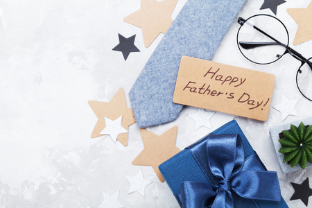 Gift or present box, paper tag with Happy Fathers Day, eyeglasses and necktie on white table top view. Flat lay composition. Reklamní fotografie