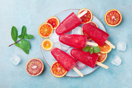 Homemade citrus ice cream or popsicles decorated mint leaves and orange slices on blue table top view. Frozen fruit juice.