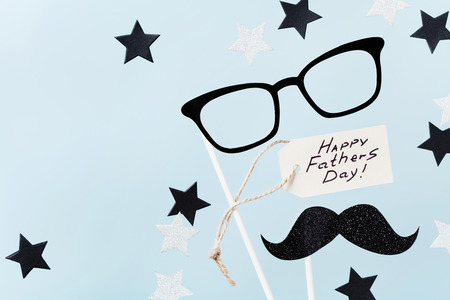 Happy Fathers Day background with greeting tag, glasses, funny moustache and star confetti on table top view. Flat lay composition.