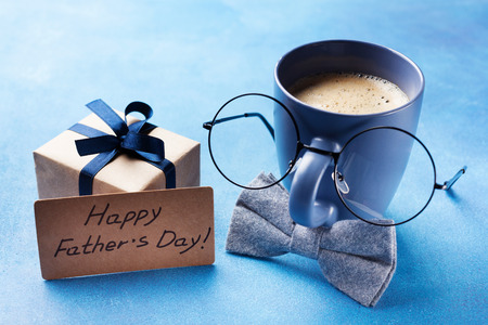 Creative breakfast on Happy Fathers Day with gift box, funny face from cup of coffee, eyeglasses and bowtie. Standard-Bild - 101804512