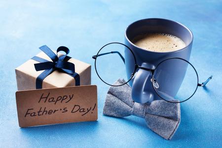 Kreatives Frühstück am glücklichen Vatertag mit Geschenkbox, lustigem Gesicht von Tasse Kaffee, Brille und Fliege.