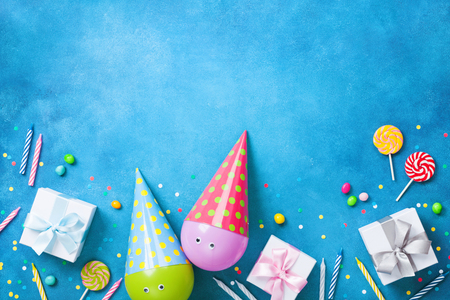 Holiday background with funny balloons in caps, gifts, confetti, candy and candles. Flat lay. Birthday or party greeting card with copy space. Stock Photo
