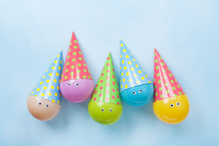 Colorful funny balloons on blue table top view. Festive or party background. Flat lay. Birthday greeting card.
