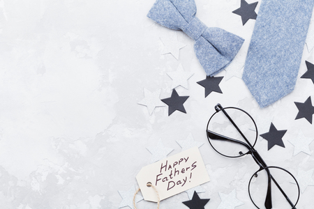 Happy Fathers Day background with greeting tag, glasses, necktie, bowtie and star confetti on table top view. Flat lay composition. Reklamní fotografie