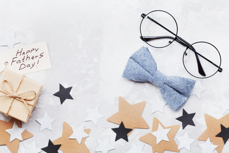 Happy Fathers Day background with paper tag, gift box, glasses and bowtie on table top view in flat lay style. Reklamní fotografie