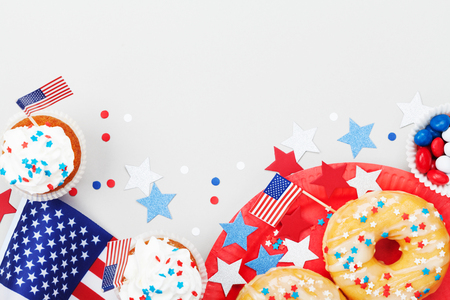 Holidays 4th july background with american flag decorated of sweet foods, stars and confetti. Happy Independence Day table top view.
