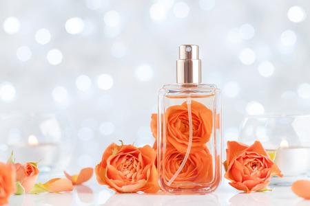Botella de perfume y flores color de rosa en el cuadro blanco contra el bokeh. Fondo de belleza y perfumería.