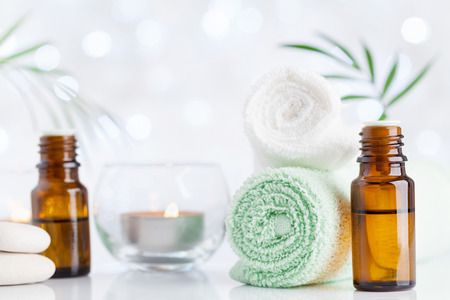 Spa, aromatherapy, wellness, beauty background. Essential oil bottle, towel and candles on white table. Stock Photo