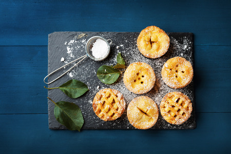 Mini apple pies decorated sugar powder on blue table from above. Delicious autumn pastry dessert.