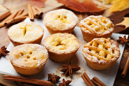 Tasty homemade apple pies on wooden board. Autumn pastry dessert.