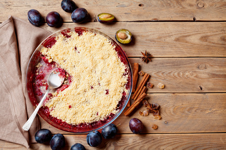 Plum crumble with aromatic spice on wooden rustic table top view. Autumn pastry. Stockfoto