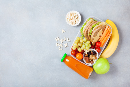 School lunch box with vegetables, fruits and sandwich on table top view.