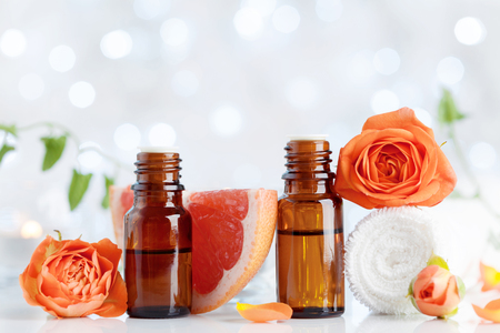 Essential oil bottles with towel, grapefruit and rose flowers on white table. Spa, aromatherapy, wellness, beauty background. Bokeh effect.