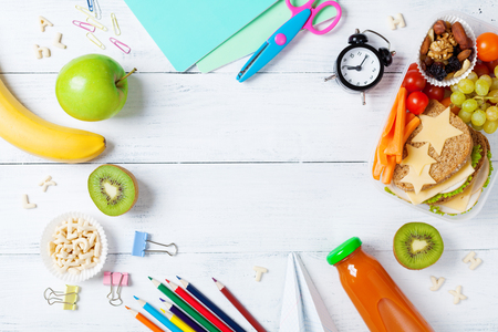 Back to school concept. Healthy lunch box and colorful stationery on white wooden table top view.