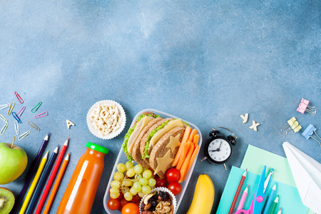 Back to school concept. Healthy lunch box and colorful stationery on blue table top view. Stock fotó