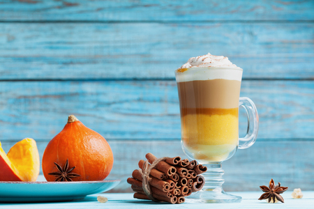 Pumpkin spiced latte or coffee in glass on turquoise rustic table. Autumn, fall or winter hot drink. Stock Photo