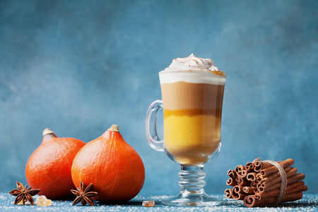 Pumpkin spiced latte or coffee in glass on dark blue table. Autumn, fall or winter hot drink.
