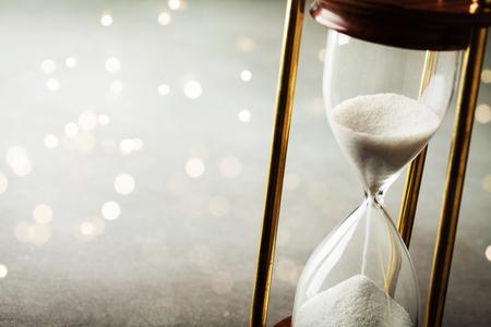 Zand loopt door de zandloper. Tijdwaarnemer concept. Boke-effect.