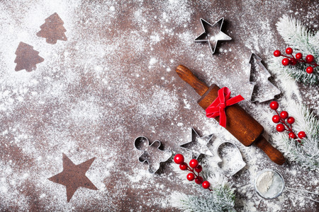 Christmas baking background with flour and rolling pin decorated with fir tree top view.