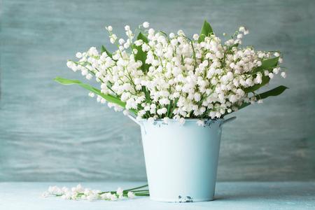 Flores de lirio de los valles en florero azul sobre mesa rústica. Ramo de aroma primaveral.
