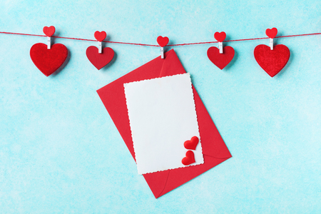 Valentines day background. Garland of red hearts on clothespins and envelope with card on turquoise wall.