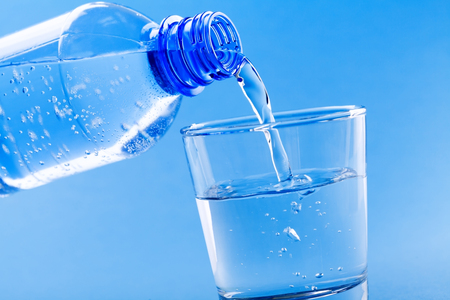 Pouring drinking water from bottle into glass on blue background. Imagens