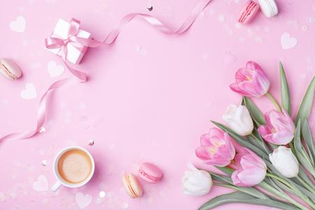 Poranna kawa, ciasto makaronik, pudełko na prezent lub teraźniejszość i wiosenne kwiaty tulipanów na różowym tle. Piękne śniadanie na Dzień Kobiet, Dzień Matki. Leżał płasko. Zdjęcie Seryjne