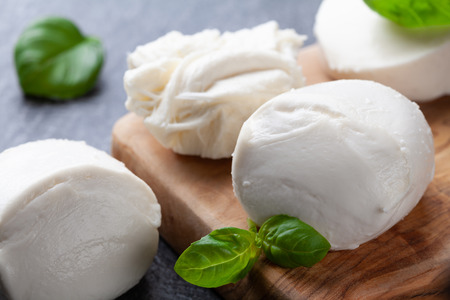Mozzarella cheese with basil on wooden board. Natural italian dairy product.