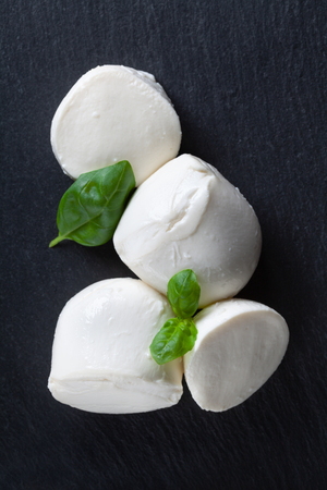 Mozzarella cheese with basil on black table top view. Natural italian dairy product. 写真素材 - 120432167