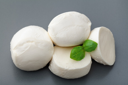Mozzarella cheese with basil on stone table. Natural italian dairy product. Imagens
