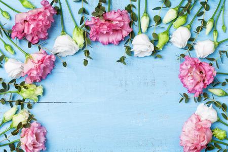 Tarjeta de felicitación del día de la madre. Hermosas flores de primavera en la vista superior de la mesa de madera azul. Endecha plana.