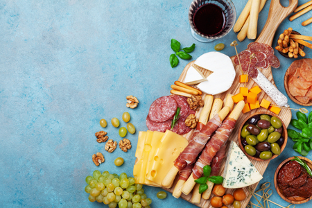 Italian appetizers or antipasto set with gourmet food on blue table top view. Mixed delicatessen of cheese and meat snacks with glass of wine.
