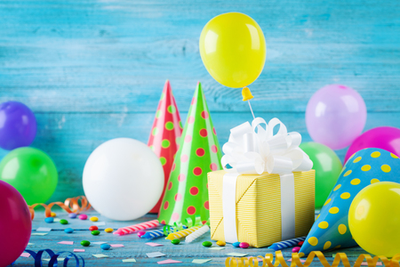 Birthday party background with gift or present box, colorful balloons, confetti, carnival cap and streamer. Holiday supplies on blue table. Standard-Bild