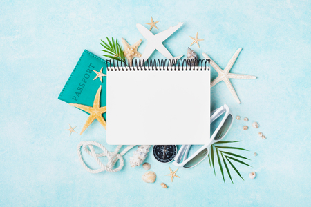 Open notebook with accessories on blue pastel table top view. Planning summer holidays, travel and vacation background. Flat lay style.